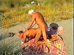 Bronzeada em pêlo paizinhos de de praia, com espectador