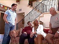 Loira cougar com grandes mamas cavalga um galo jovem em um sofá enquanto relógios marido