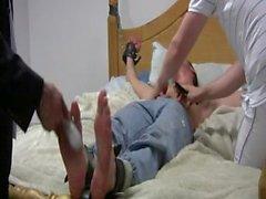 Dave amarrado à cama sendo cócegas por Simon e Chris