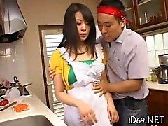 del ama de casa Asiático de obtiene quitó en su cocina del