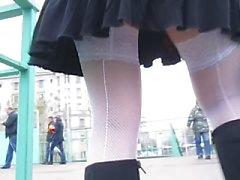Menina em brancas meias arrastão com costura vai no andar de cima