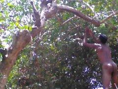 Village Boy Nude I skogen och leka med träd