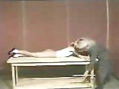 Adolescente loira fica caned deitada sobre uma mesa