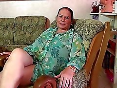 Chubby mature lady oiling up her tits and toying h