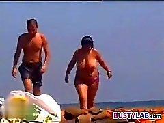 Donna spessa Wth Tettone ad una spiaggia