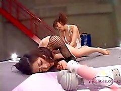 Dos niñas asiáticas lucha estímulo y mierda el uno al otro con juguetes sobre la del estera de lucha