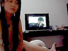 Menina chinesa de bonita dá a um broche