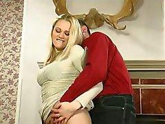 Rondborstige blonde zet op een strapon om haar man neuken in femdom clip