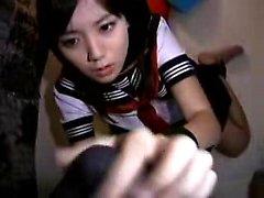 adolescente asiático con un traje de marinero se dedos y sopla antes