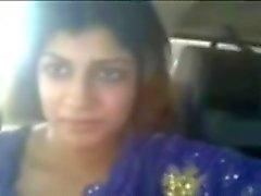 Intialainen pullukka porton vilkuttaa hänen rintojaan autossa