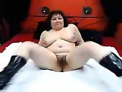 Busty reife Dame in schwarzen Stiefeln zeigt ihre behaarte Fotze auf