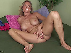 Aged doxy inserts weenie-shaped sex-toy in her slit!