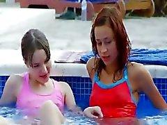 Natte lezzies kussen door het zwembad