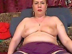 Storbröstade moget kvinna i strumpor sveper sina läppar aroun