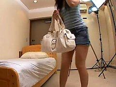 Hinreißend japanischen Mädchen liegt auf dem Bett und macht ihre WIG-