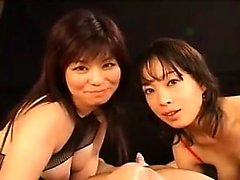 Två provokativa orientaliska damer i fisknät mjölkar hårt