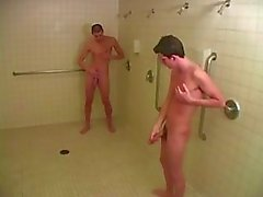 Two horny young gay guys in shower having hot blowjob