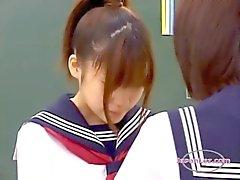 2 Schoolmeisjes zoenen klopte Terwijl Standing In The Classroo