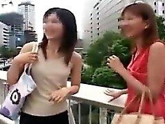 Duas senhoras asiáticas bonitas deixam cair suas roupas e ostentam