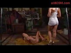 Blackhaired Girl With Tied Legs And Arms Getting Her Mouth And Pussy Fucked With Dildo On The Floor By Mistress In The Workshop