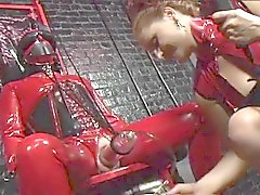 Red and black latex dominatrix BDSM torture play in this sex dungeon