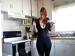 Busty redhead with a big ass is in the kitchen showing off her food
